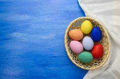 Пасхальные яйца в корзине yello на предпосылках S1V12 сини и ткани Стоковое фото RF