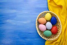 Пасхальные яйца в корзине yello на предпосылках S1V11 сини и ткани Стоковые Фотографии RF