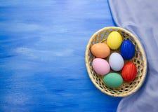 Пасхальные яйца в корзине yello на предпосылках S1V10 сини и ткани Стоковое фото RF