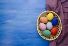 Пасхальные яйца в корзине yello на предпосылках S1V9 сини и ткани Стоковое Изображение