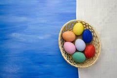 Пасхальные яйца в корзине yello на предпосылках S1V8 сини и ткани Стоковые Фото