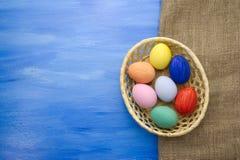 Пасхальные яйца в корзине yello на предпосылках S1V7 сини и ткани Стоковые Фотографии RF