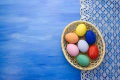 Пасхальные яйца в корзине yello на предпосылках S1V5 сини и ткани Стоковое Фото