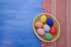 Пасхальные яйца в корзине yello на предпосылках S1V4 сини и ткани Стоковое фото RF