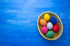 Пасхальные яйца в корзине yello на предпосылках S1V3 сини и ткани Стоковое Изображение RF