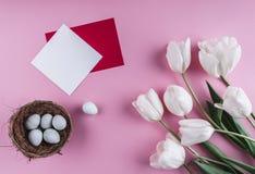 Пасхальные яйца в цветках гнезда и тюльпана на предпосылке весны Взгляд сверху с космосом экземпляра карточка пасха счастливая Стоковое Изображение RF