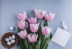 Пасхальные яйца в цветках гнезда и тюльпана на предпосылке весны Взгляд сверху с космосом экземпляра карточка пасха счастливая Стоковое Фото