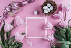 Пасхальные яйца в цветках гнезда и тюльпана на предпосылке весны Взгляд сверху с космосом экземпляра карточка пасха счастливая Стоковые Фотографии RF