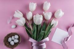 Пасхальные яйца в цветках гнезда и тюльпанов на предпосылке весны Взгляд сверху с космосом экземпляра карточка пасха счастливая Стоковое Фото