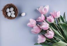 Пасхальные яйца в цветках гнезда и тюльпанов на предпосылке весны Взгляд сверху с космосом экземпляра карточка пасха счастливая Стоковая Фотография