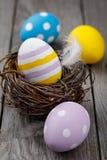 Пасхальные яйца других цветов на деревянном столе Стоковые Изображения