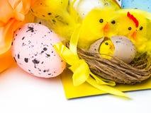 Пасхальные яйца и желтые цыплята на белой предпосылке стоковое изображение