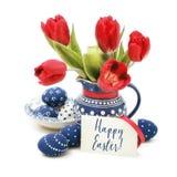 Пасхальные яйца и красные тюльпаны в голубой керамике на белизне, тексте Стоковое фото RF