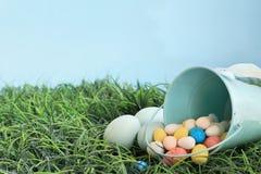 Пасхальные яйца и яйца солода конфеты в траве стоковые изображения