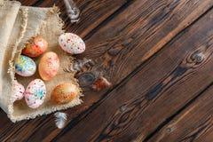 Пасхальные яйца создали программу-оболочку в ткани холста на деревянной предпосылке стоковое изображение
