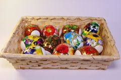 Пасхальные яйца с первоначально картиной в корзине на таблице стоковые изображения rf
