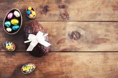 Пасхальные яйца шоколада на деревянной предпосылке с смычком ленты и c Стоковые Фотографии RF