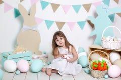 Пасха! Красивая маленькая девочка в белом платье с пасхальными яйцами и корзина около ярких украшений Зайчик и морковь пасхи стоковое изображение rf