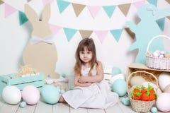Пасха! Красивая маленькая девочка в белом платье с пасхальными яйцами и корзина около ярких украшений Зайчик и морковь пасхи стоковое изображение