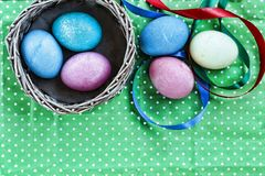 Пасха Пасхальные яйца в корзине на зеленой предпосылке и покрашенных лентах пасха счастливая Стоковое Фото