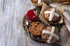 Пасха пересекает булочки с изюминками, клюквами и вареньем поленики Стоковое Изображение