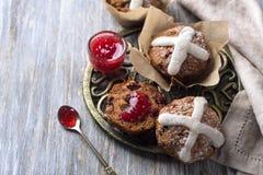 Пасха пересекает булочки с изюминками, клюквами и вареньем поленики Стоковые Изображения