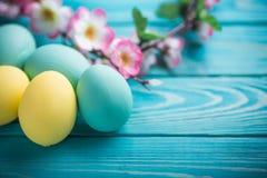 Пасха покрасила яичка с лентой шнурка и цветки на голубой деревянной предпосылке Стоковые Фото