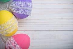 Пасха покрасила яичка с лентой шнурка на белой деревянной предпосылке Стоковое Изображение RF