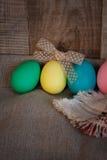 Пасха покрасила яичка с смычком против естественной деревянной текстурированной предпосылки Стоковая Фотография