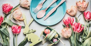 Пасха составляя с тюльпанами весны, оформлением зайчика, яичками и праздничной сервировкой стола с плитой и столовым прибором Стоковые Фото