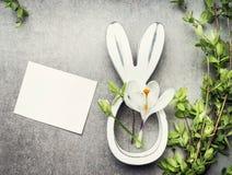 Пасха составляя с пустыми белыми карточкой, хворостинами весны, цветками и оформлением зайчика Стоковая Фотография