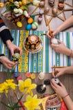пасха счастливая Группа людей крася пасхальные яйца на деревянном столе Счастливая семья подготавливая для пасхи процесс  Стоковое Изображение