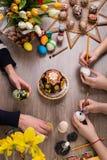 пасха счастливая Группа людей крася пасхальные яйца на деревянном столе Счастливая семья подготавливая для пасхи процесс  Стоковые Фотографии RF
