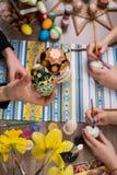пасха счастливая Группа людей крася пасхальные яйца на деревянном столе Счастливая семья подготавливая для пасхи процесс  Стоковые Фото