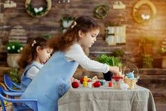 пасха счастливая Двойные дети девушек имея краску потехи и украшают яичка на праздник стоковое изображение rf