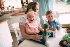 пасха счастливая Мать и ее дети крася пасхальные яйца Стоковая Фотография RF