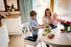 пасха счастливая Мать и ее дети крася пасхальные яйца Стоковая Фотография