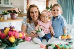 пасха счастливая Мать и ее дети крася пасхальные яйца Стоковое Фото