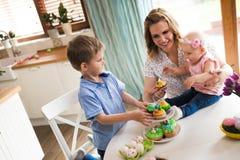 пасха счастливая Мать и ее дети крася пасхальные яйца Стоковое Изображение RF