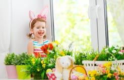 Пасха счастливая девушка ребенка с ушами зайчика и красочным sitti яичек Стоковые Фотографии RF