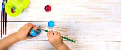 пасха счастливая Мать и ребенк крася пасхальные яйца Стоковое Фото