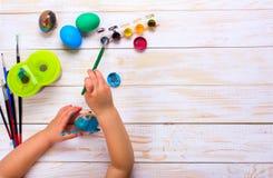 пасха счастливая ребенк крася пасхальные яйца Стоковая Фотография RF