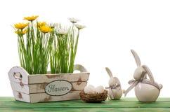 Пасха - цветки в деревянной коробке и керамических зайчиках Стоковое Изображение RF