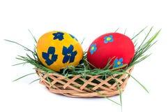 2 пасхального яйца в корзине на белой предпосылке Стоковые Фотографии RF