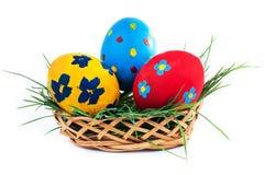 3 пасхального яйца в корзине на белой предпосылке Стоковая Фотография