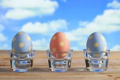 3 пасхального яйца в пастельных цветах на деревянном столе Стоковое Изображение RF