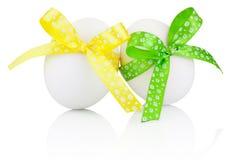 2 пасхального яйца при зеленый и желтый изолированный смычок ленты Стоковое Фото