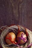 2 пасхального яйца с яркими лентами в гнезде Стоковые Изображения RF