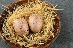 2 пасхального яйца триперсток на деревянной плите с сеном Стоковая Фотография RF