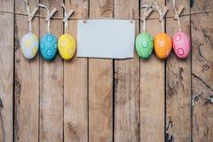 Пасхальное яйцо и чистый лист бумаги для смертной казни через повешение ярлыка на деревянной предпосылке Стоковое Изображение